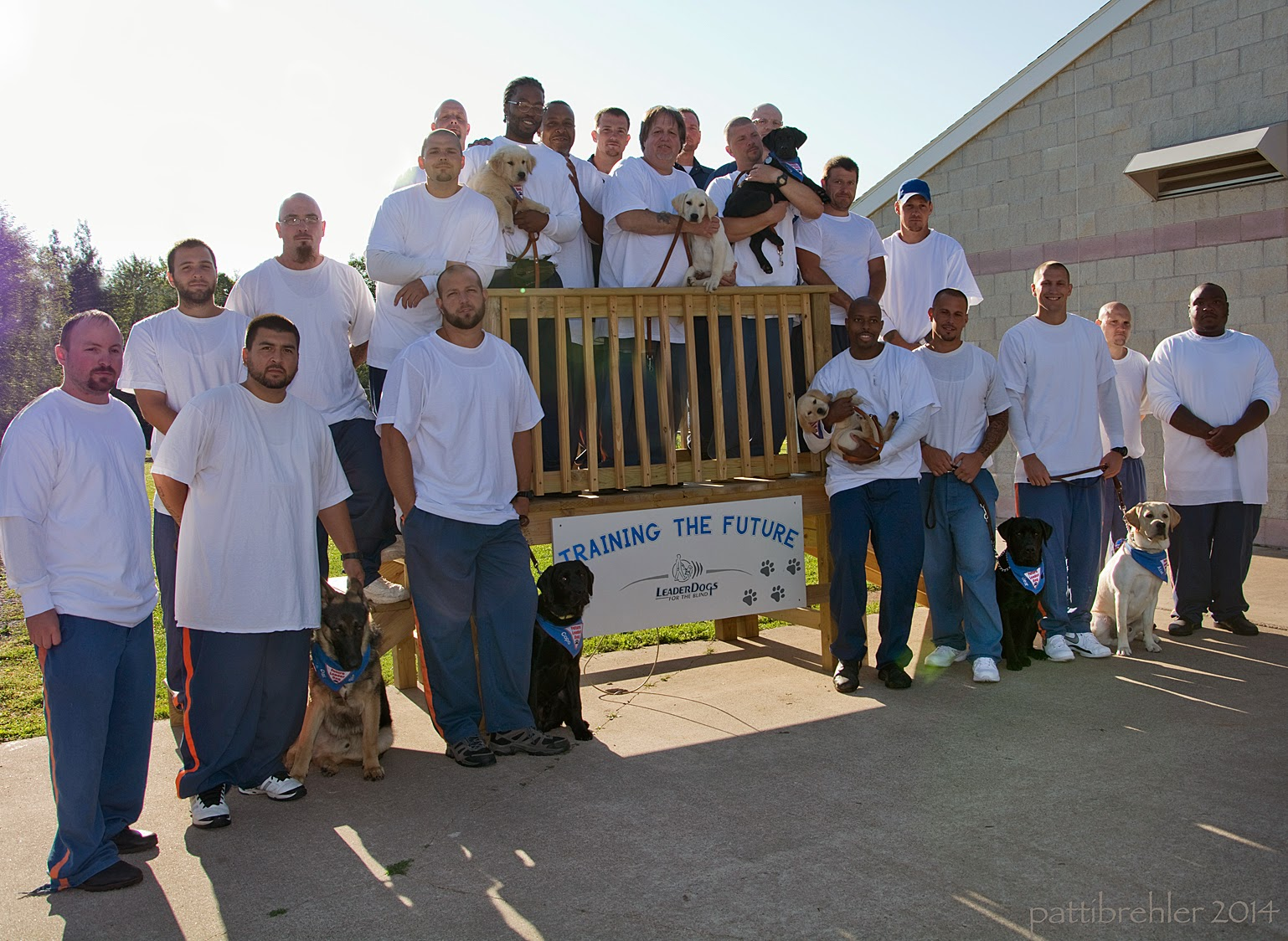 "At least 21 men dressed in blue prison pants and white -shirts stand next to and on a wooden staircase that is standing on pavement next to a white brick building. There is a sign attached to the staircase in the middle that reads ""Training the Future"" with the Leader Dogs for the Blind logo. Eight puppies are either sitting next to a man or being held by a man. The stairs are outside in bright sunshine."