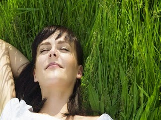 A lady sleeping on the grass.