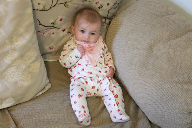 baby sitting up on sofa wearing a red and white floral sleepsuit and pink bib