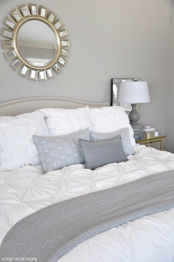 neutral master bedroom,  white bedding, gray pillows and accents, sunshine mirror