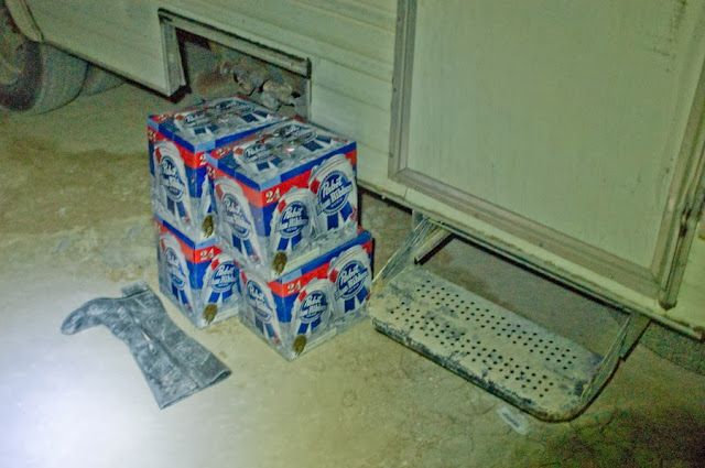 stack of pbr outside of an RV at the burn