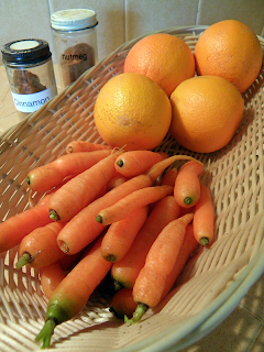 Basket of Carrots and Oranges with Spice Jars in Background