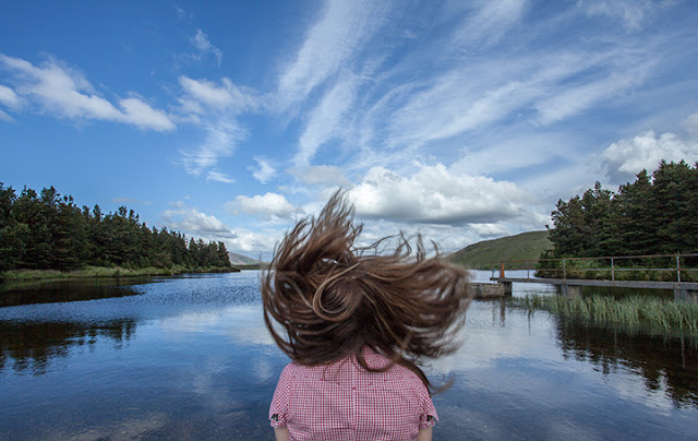 Girl standing in front of a serene lake with hair thrown up in the air.