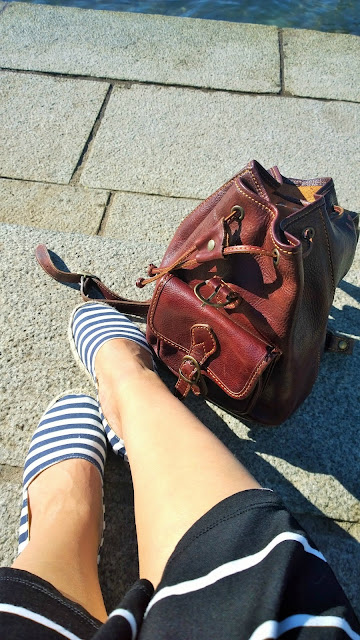 Striped espadrilles, brown backpack; sitting at the shore of Lake Iseo
