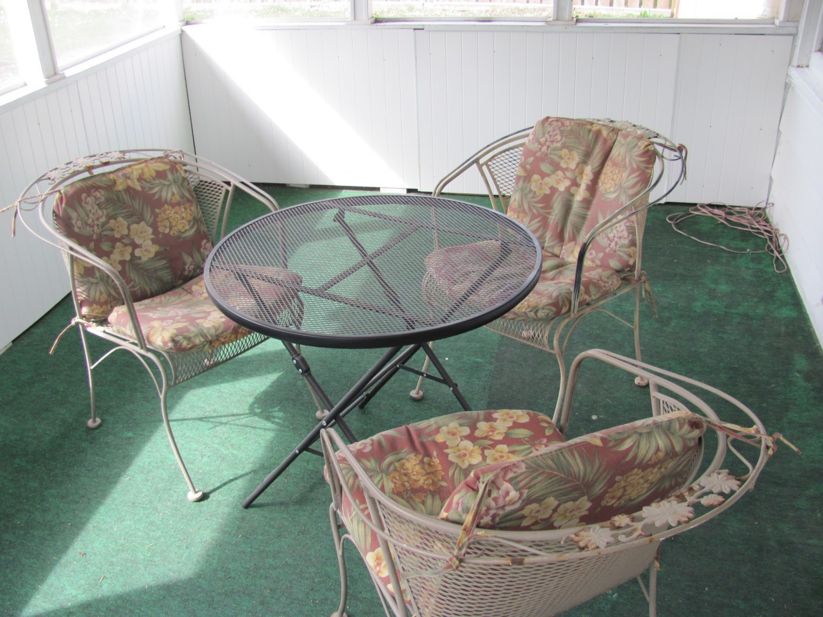 Set of three iron chairs with a black folding outdoor table