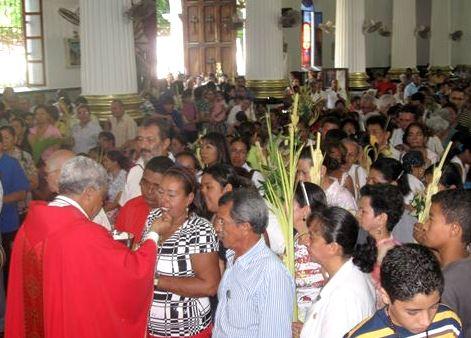 Personas en la iglesia por Domingo de Ramos (Padre dando el hostia a una mujer)