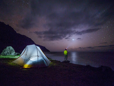 man wearing headlamp, looking out over lake on a starry night, with a tent on the shore lit from within
