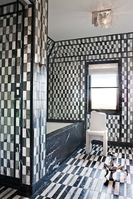 Black and white marble floor to ceiling bathroom tile and a small robot