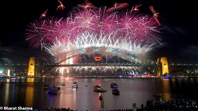 It was New Year, when Bharat and Ishita flew to Australia from New Zealand for celebrations. This Photo Journey shares some of the moments from Sydney Harbour, where some amazing fireworks were captured on New Year Evening. Let's check out more from Sydney Harbour.Above photograph shows Sydney Harbour Bridge which is basically a steel bridge through arch bridge across Sydney Harbour that carries rail, vehicular, bicycle and pedestrian traffic between the Sydney central business district (CBD) and the North Shore. The dramatic view of the bridge, the harbour, and the nearby Sydney Opera House is an iconic image of Sydney, New South Wales, and Australia. The bridge is nicknamed 'The Coathanger' because of its arch-based design.In midnight, Australia celebrates the start of a New Year! Sydney does this in style by lighting up the night sky with a spectacular fireworks display launched from seven barges on the Harbour, the rooftops of seven city skyscrapers and, unforgettably, from Sydney Harbour Bridge. It becomes a  reason why Sydney is the New Year's Eve Capital of the World.Many of the folks come to Australia for New Year Celebrations. Many folks don't get right place at Sydney Harbour foreshore to watch what is clearly the best New Year's Eve fireworks display on Earth. This firework shows is quite popular and there are some online services providers who stream live view from a great place and these models work very well.Dawes Point, Garden Island, Sydney Cove and Vaucluse are some of the main places at Sydney Harbour. Few helicopter cameras keep capturing the great moments for online folks. The bridge's design was influenced by the Hell Gate Bridge in New York. It was the world's widest long-span bridge, at 48.8 meters wide, until construction of the new Port Mann Bridge in Vancouver. It is also the fifth longest spanning-arch bridge in the world, and it is the tallest steel arch bridge, measuring 134 metres from top to water level. Until 1967 the Harbour Bridge was Sydney's tallest structure.