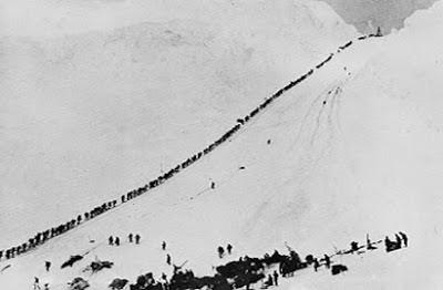 Cette image est une photo montrant le col du Chilkoot ou chilkoot Pass pendant la ruée vers l'or du Klondike à la fin du XIXème siècle. Le col du Chilkoot (ou Chilkoot Pass en anglais) est un col de montagne qui passe à travers les Coast Mountains à la frontière entre l'Alaska (États-Unis) et la province de Colombie-Britannique (Canada). Il est le point culminant du Chilkoot Trail qui mène de la ville de Dyea au Lake Bennett, en Colombie-Britannique. Pendant la ruée vers l'or du Klondike, entre 20 000 et 30 000 personnes traversèrent le col (1897-1898). Un flux continu de personnes l'empruntaient, de jour comme de nuit, et il fallait parfois attendre jusqu'à 4 heures pour pouvoir le gravir. La Police montée du Nord-Ouest y établit un poste pour assurer l'ordre, percevoir un droit de passage et s'assurer que chacun ait suffisamment de provisions pour un an, afin d'éviter les famines. Les pentes du Col Chilkoot étaient très escarpées et l'ascension dangereuse. L'altitude augmentait de 300 mètres sur une distance de 800 mètres, ce qui constitue un dénivelé important. La pente était trop raide pour que des animaux puissent franchir le col ; les mineurs devaient donc porter eux-mêmes leurs vivres et leur équipement jusqu'au sommet. Près de 1 500 marches furent creusées dans la glace pour faciliter l'ascension. L'image montre précisément l'ascension de ce col par les futurs chercheurs d'or disposés en file indienne. Ils constituent ainsi une longue procession dont la ligne noire se démarque nettement sur la blancheur de la neige. Cette image très connue est en quelque sort devenue le symbole de la ruée vers l'or du Klondike (en anglais Klondike Gold Rush) quelquefois aussi appelée ruée vers l'or de l'Alaska et plus rarement ruée vers l'or du Yukon, qui fut une ruée vers l'or frénétique qui attira des dizaines de milliers d'apprentis prospecteurs du monde entier vers la rivière Klondike près de Dawson City dans le Yukon, au nord-ouest du Canada après que de l'or y fut déco