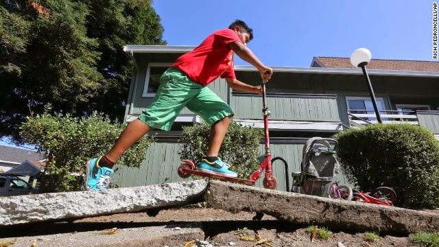 Anak laki-laki naik skuter melalui trotoar lemas oleh gempa bumi pada 24 Agustus di Napa, California.