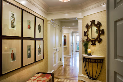 welcoming entryway with its stunning photographs display and unique table and mirror accessories
