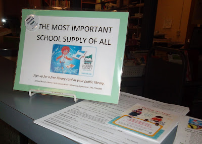 Sign on counter-top reads, 'The Most Important School Supply of All. Sign up for a free library card at your public library.' Below, it displays information for Ashland Branch Library, 410 Siskiyou Blvd., Children's Department: 541-774-6995