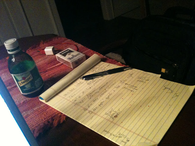 Cigarettes, ginger ale, boston baked bean crumbs, a pen, yellow lined paper.