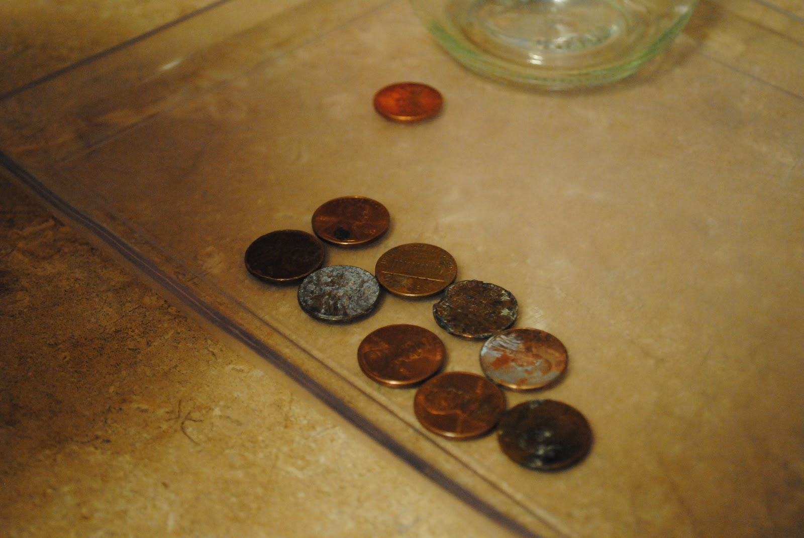 Found nine dirty pennies foreground and one clean penny background