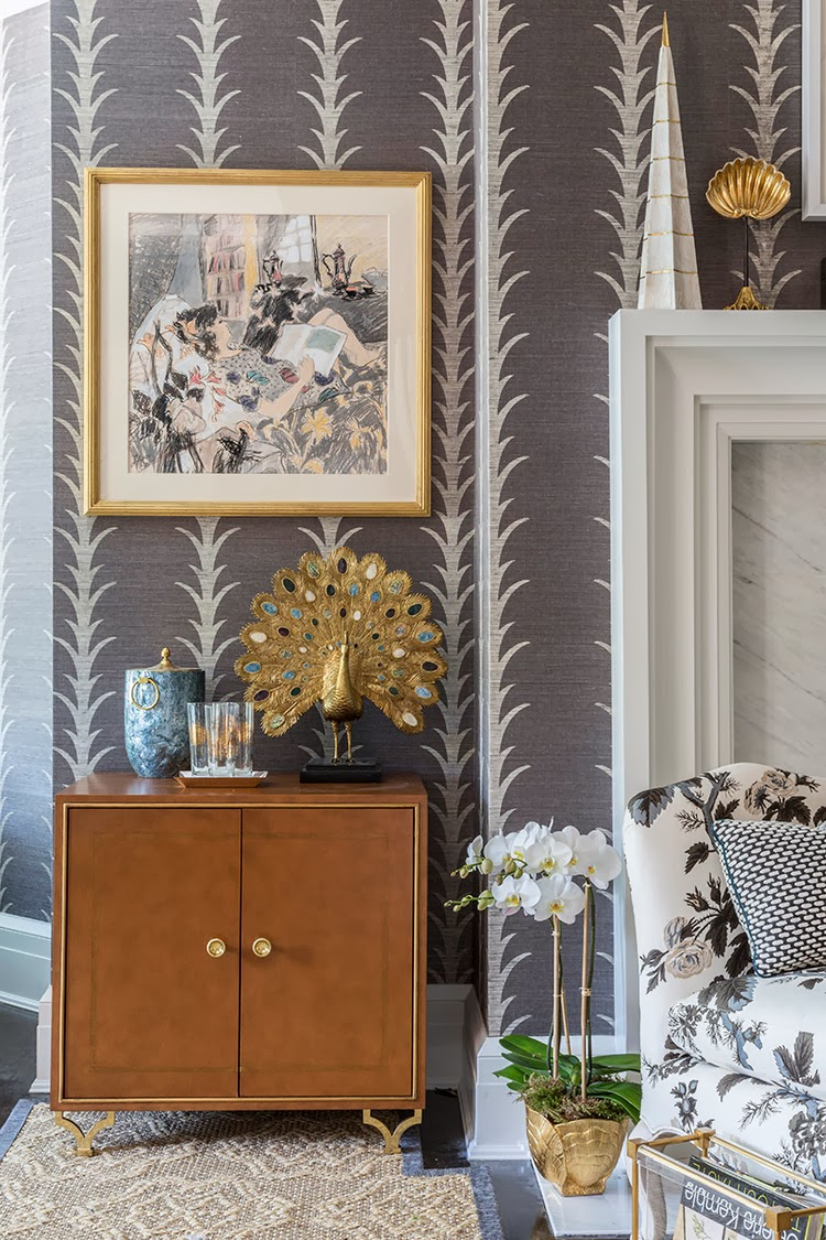 Close up of a wood cabinet in a Hamptons bedroom with grape vine wallpaper and a gold peacock