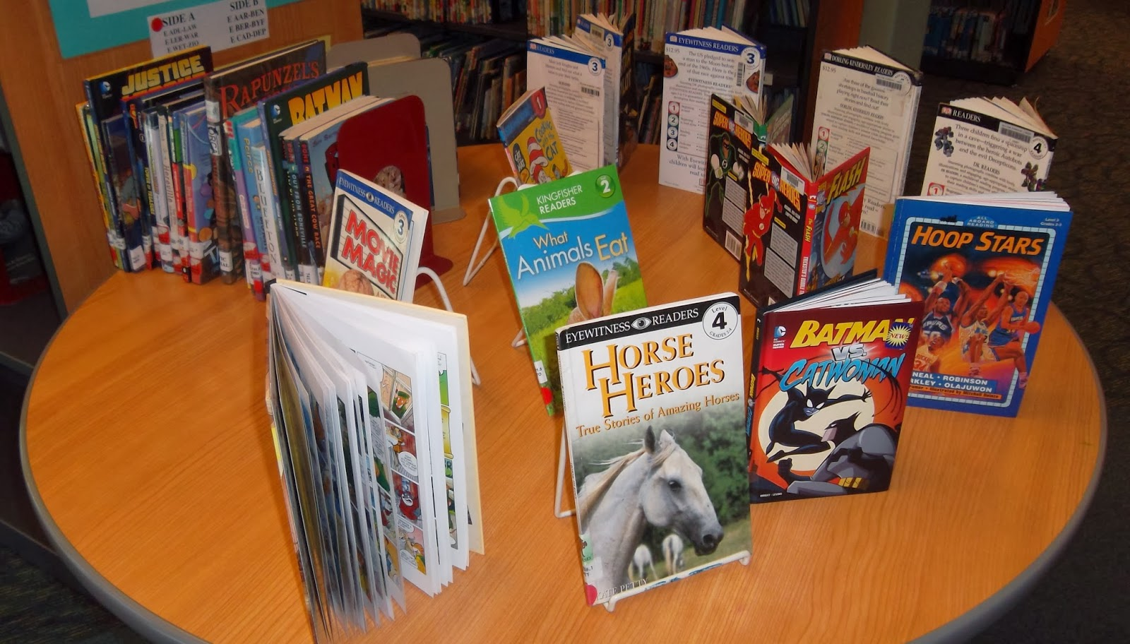 Group of graphic novels and early-reader children's books arranged in a display on a circular table-top