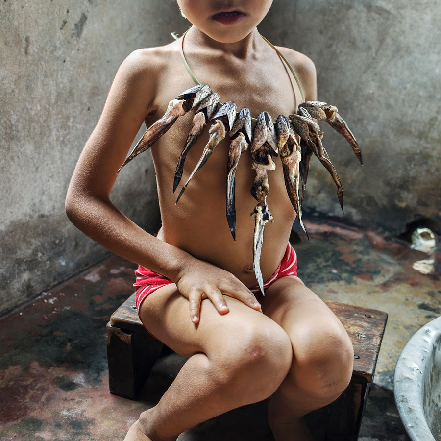 Photo of a little Indian girl wearing a large necklace made out of fish skeletons