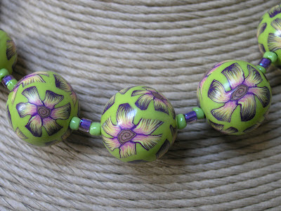 Polymer clay beads decorated with slices from a flower cane