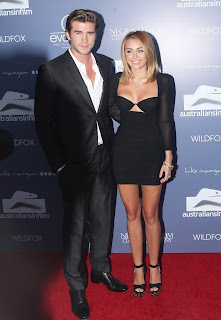 Miley Cyrus and fiance posing for cameras at AIF red carpet