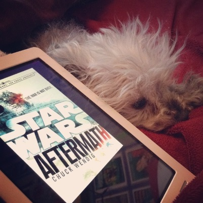 Murchie flops atop a red blanket, his chin to one side of a his crossed paws. In front of him is a white Kobo with Aftermath's cover on its screen. The cover features an exploding Death Star above the title, which slopes diagonally across a white background.