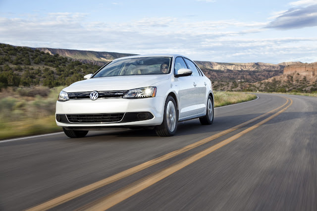 White 2013 Volkswagen Jetta Hybrid front 3/4 shot driving along a two-lane Arizona highway