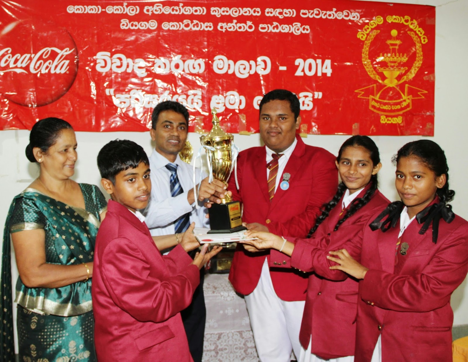 Ruwan Kumara Public Affairs and Communications and SRA Manager at Coca-Cola Beverages Sri Lanka Ltd hands over trophy to Victorious Siyamabalapewatte Kanishta Vidyalaya Team, winners of the second category
