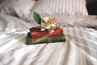 books and flowers on a bed