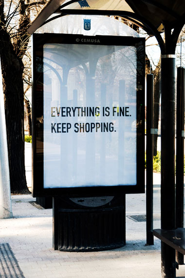 Image of a bus shelter and advert which reads, 'Everything is fine. Keep shopping.'