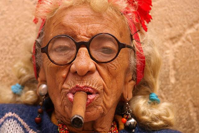 """""""<a href=""""https://commons.wikimedia.org/wiki/File:Cigar_smoking_woman_in_Cuba.jpg#/media/File:Cigar_smoking_woman_in_Cuba.jpg"""">Cigar smoking woman in Cuba</a>"""" by <a rel=""""nofollow"""" class=""""external text"""" href=""""https://picasaweb.google.com/105432035598159259077"""">Tibor Végh</a> - <a rel=""""nofollow"""" class=""""external text"""" href=""""https://picasaweb.google.com/105432035598159259077/KozepEsDelAmerikaiPortrekFeltoltesAlatt#5347515123466409570"""">Kuba 996.jpg</a>. Licensed under <a href=""""http://creativecommons.org/licenses/by/3.0"""" title=""""Creative Commons Attribution 3.0"""">CC BY 3.0</a> via <a href=""""//commons.wikimedia.org/wiki/"""">Wikimedia Commons</a>."""