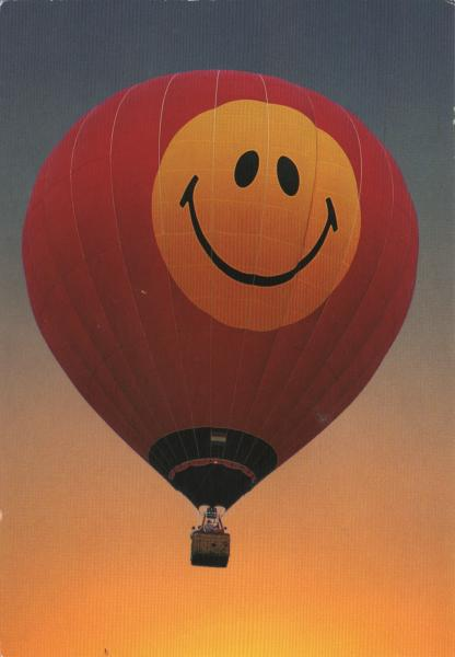 hot air balloon with a Mr Happy face on it, in flight