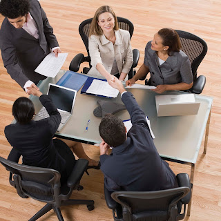 Picture of a business meeting, with six participants smiling and shaking hands.