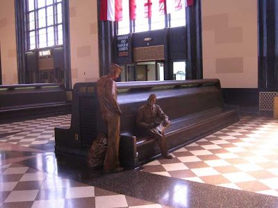 The waiting room with long benches, checkered pattern on floor. Two sculptures of soldiers sit and stand as if talking