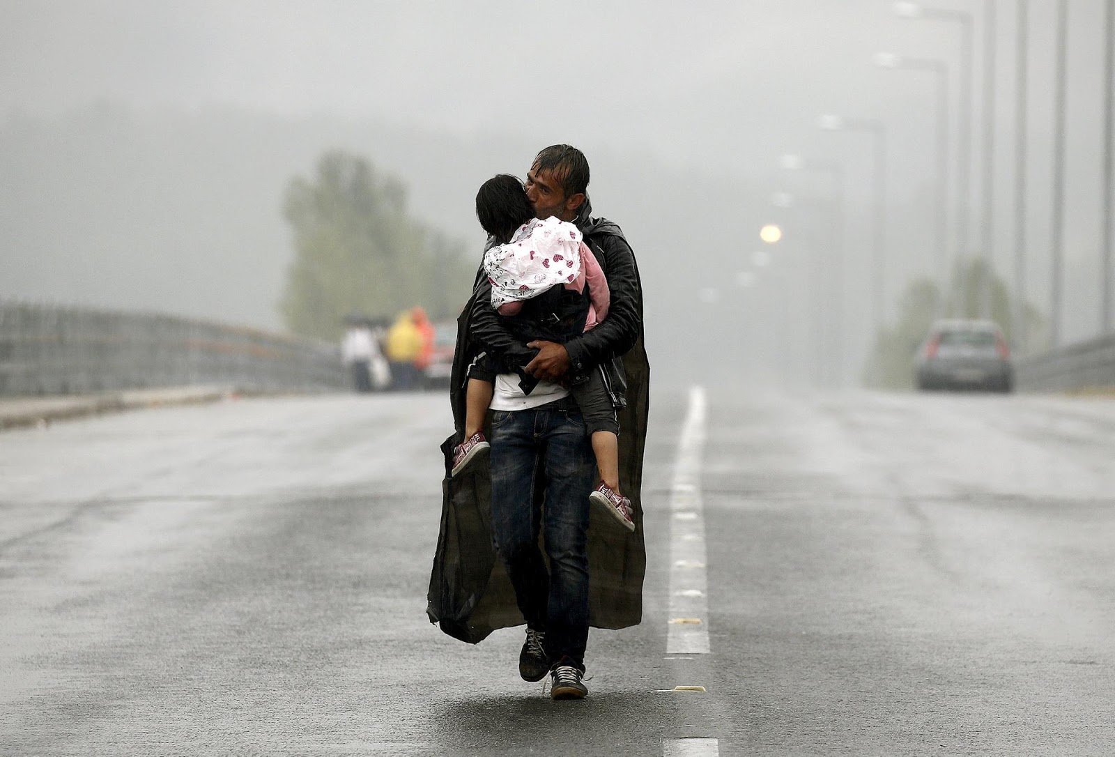 70 Of The Most Touching Photos Taken In 2015 - A Syrian refugee kisses his daughter as he walks through a rainstorm towards Greece's border with Macedonia, in September.