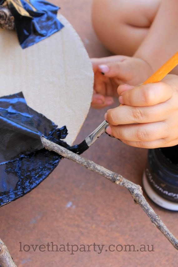 child painting giant black spider lantern DIY for Halloween