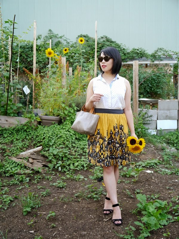 Sleeveless swiss dot blouse, patterned yellow skirt, black suede sandals, cat-eye shades