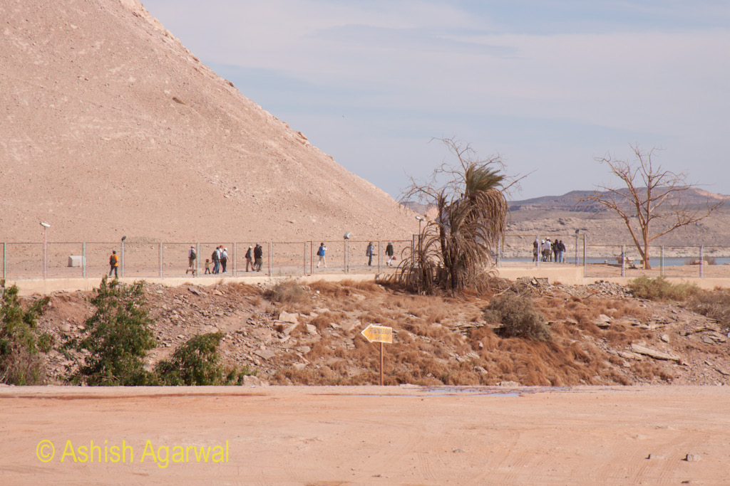 Tourists walking around the edge of the hillock at the Abu Simbel temple in Egypt