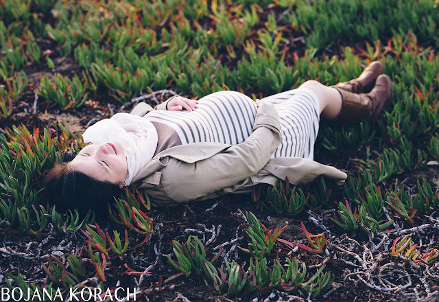 pregnant woman laying on the ground touching her pregnant belly captured by san francisco photographer