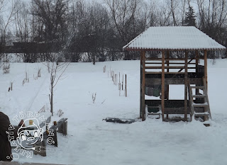 Szöveg: ... és reggel. Kép: Ugyanaz a beállás, csak most napvilágnál locsolják a havat, jeget. A víz magasból hull alá a földre.
