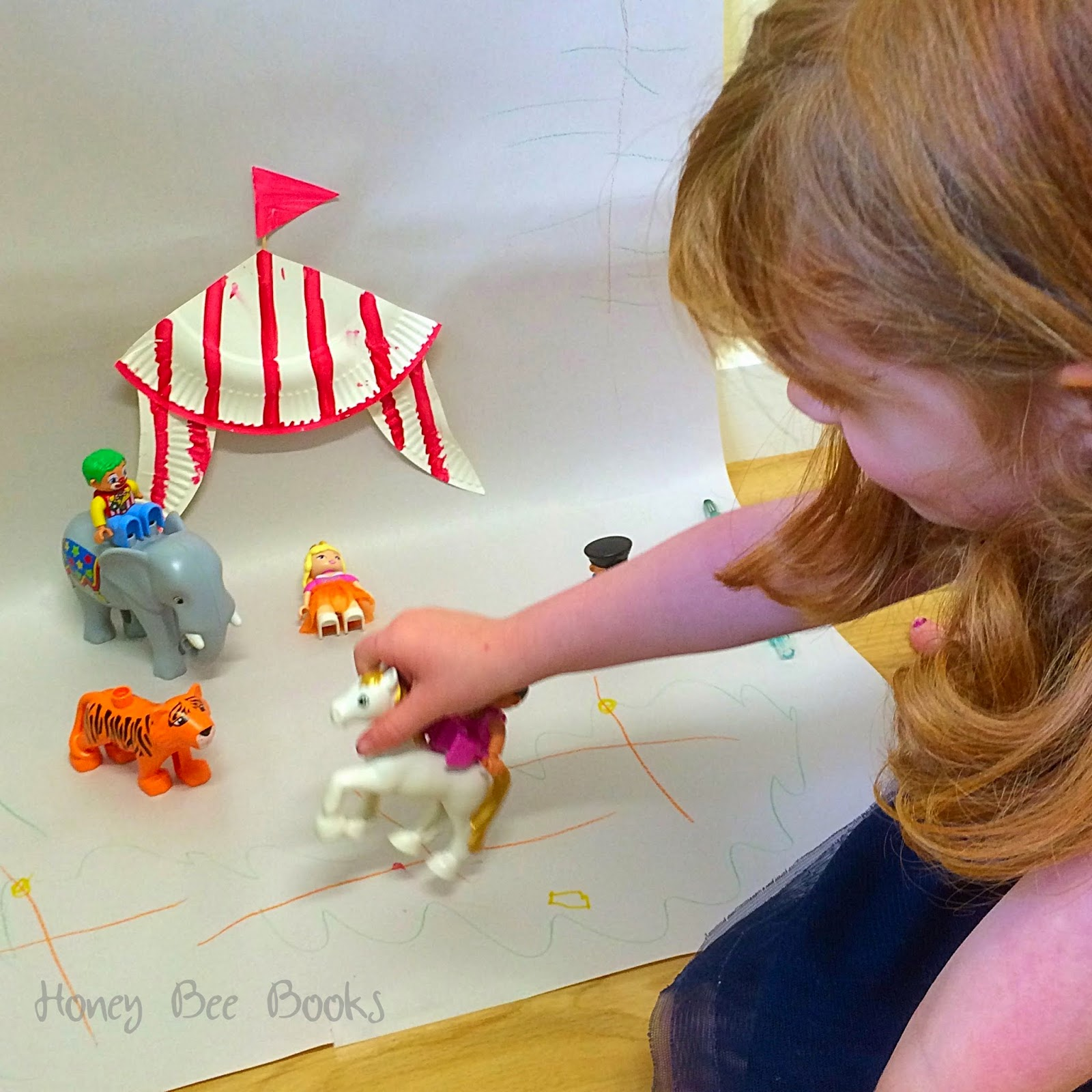 Imaginative circus play using a paper plate circus tent and circus duplo