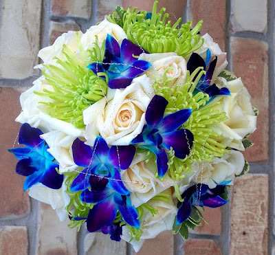 Bouquet of blue orchids and green Spider Mums. Cream roses add a beautiful contrast to the cool greens and blues.