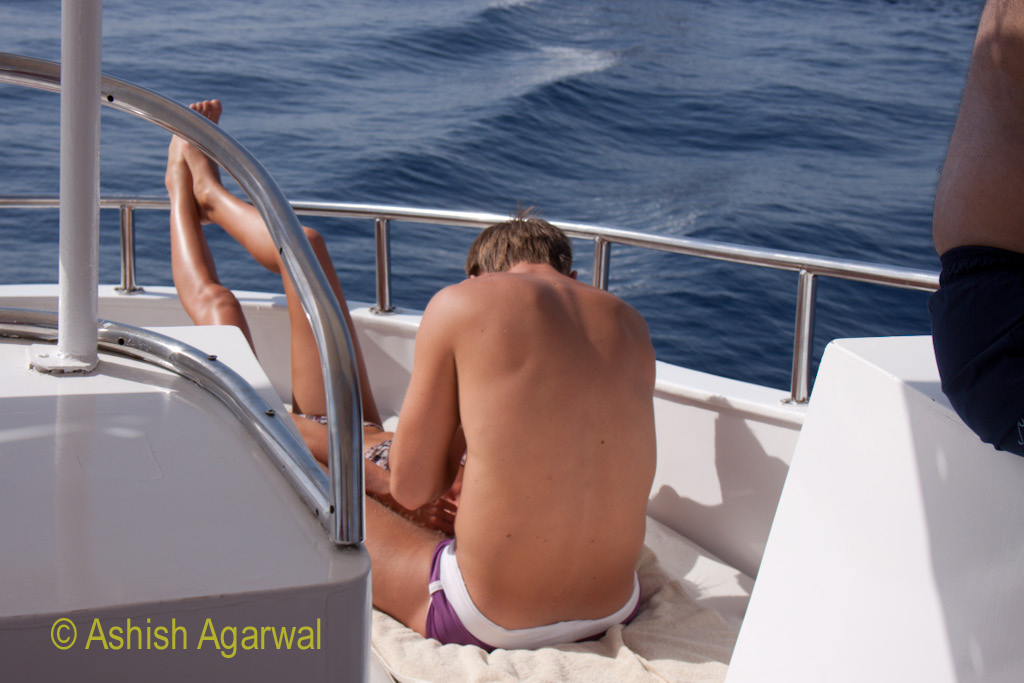 Couple sun-bathing on the lower deck of a small yacht used for tourists off the shore of Sharm el Sheikh in Egypt