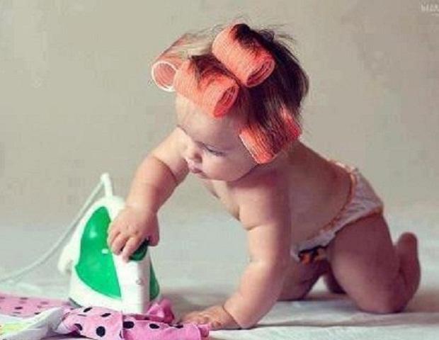 un joli bébé qui repasse ses vêtements
