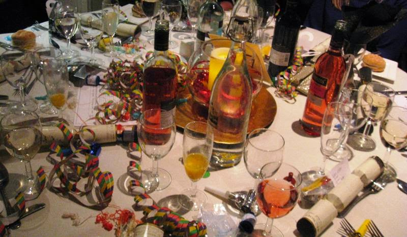 Table strewn with crackers, streamers, bottles, glasses and other party debris