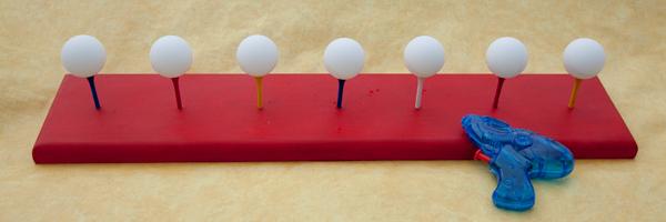un jeu d'adresse : les enfants doivent faire tomber des balles de ping pong en équilibre sur des tees de golf à l'aide de leur pistolet à eau