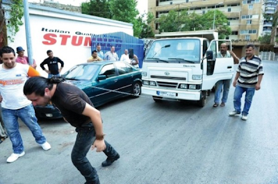 لبناني يجرّ شاحنتين بشعره