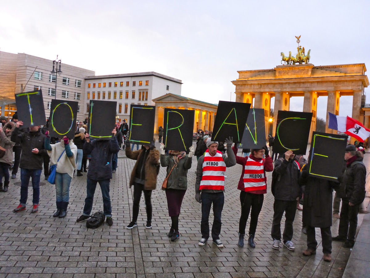 """Demonstranten halten Buchstaben vor dem Brandenburger Tor hoch, die """"TOLERANCE"""" ergeben. Im Hintergrund Brandenburger Tor, Abendlicht, die französische und die Berliner Flagge."""