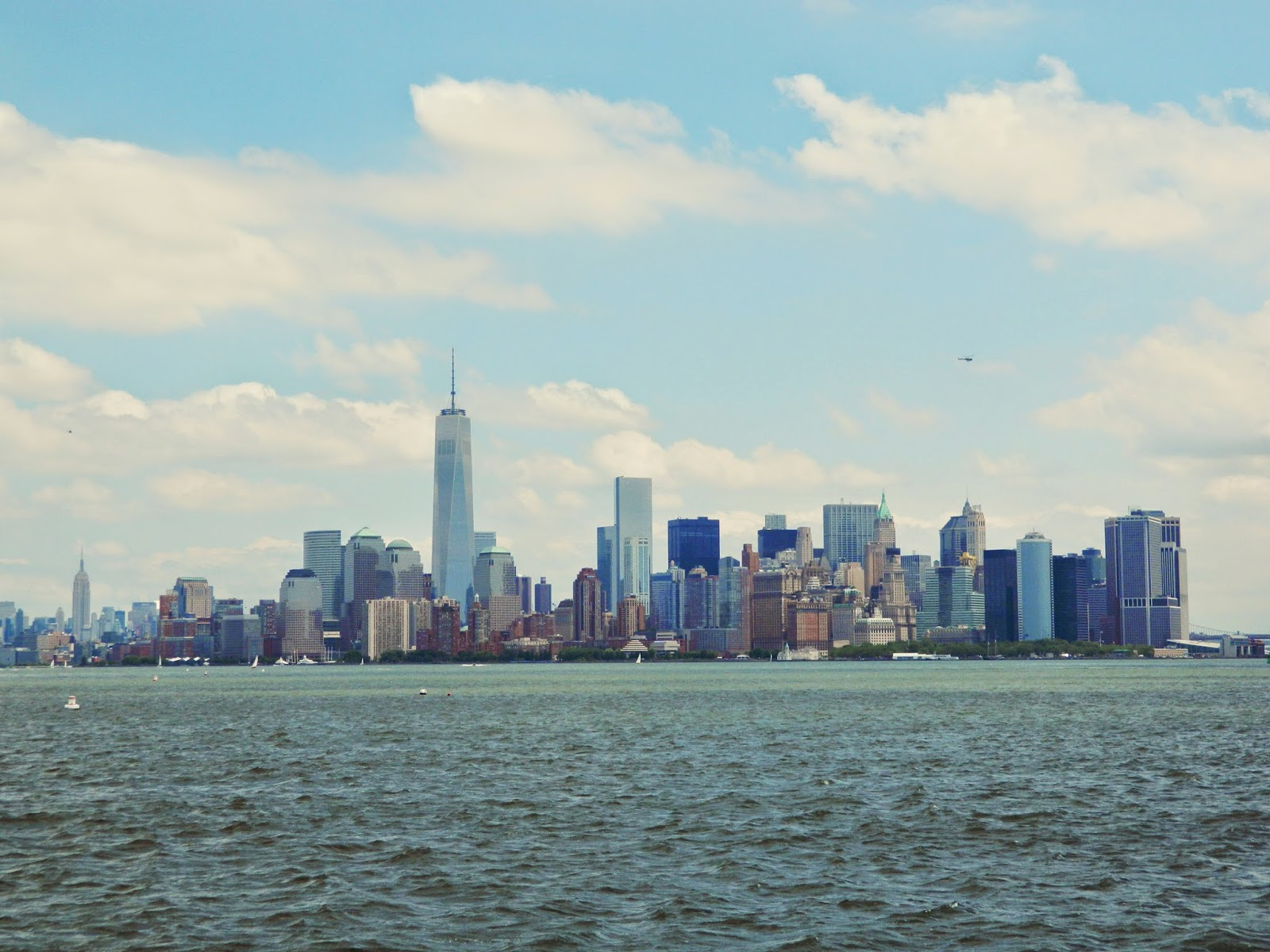 new york city skyline from statue of liberty clear day beautiful sun finance district