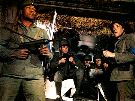 Jim Brown and Donald Sutherland wield machine guns in The Dirty Dozen movieloversreviews.blogspot.com