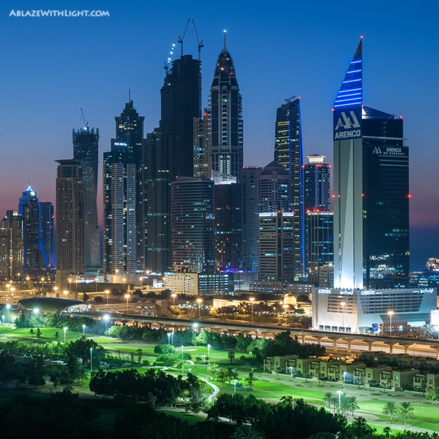 Photo of Dubai Marina skyscrapers and some large park in front of them as seen at sunset